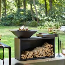 barbacoa ofyr isla negra jardin Barbacoa redonda Ofyr en acero corten color negro con mueble leñero y tabla de corte de madera o granito