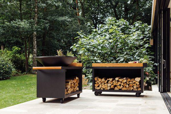 ofyr isla pro negra 100 jardin Barbacoa redonda Ofyr en acero corten color negro con mueble leñero y tabla de corte de ceramica.